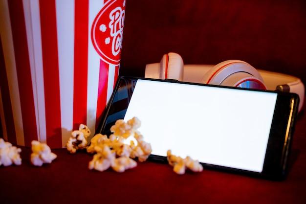 Telefone móvel com tela brilhante branca vazia com balde de pipoca no sofá vermelho Foto Premium