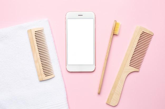 Telefone móvel e eco escova de dentes de madeira, pente, escova para massagem seca em rosa Foto Premium