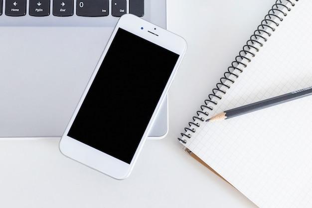 Telefone móvel, sobre, a, laptop, com, lápis, e, caderno, sobre, a, branca, tabela Foto gratuita