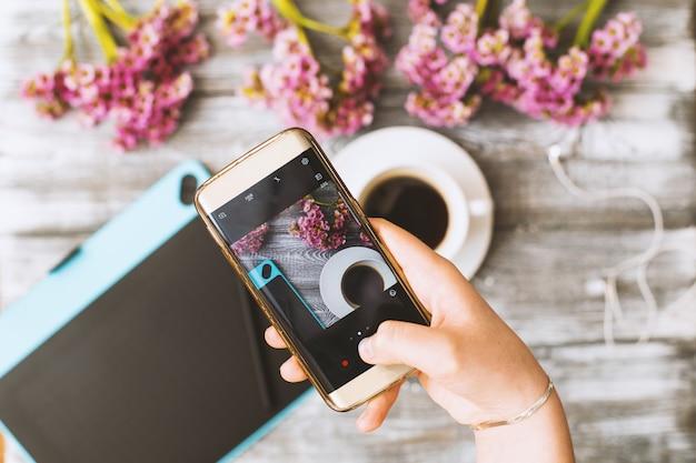 Telefone na mão toma uma xícara de café Foto Premium