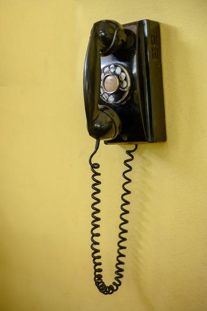 Telefone preto vintage na parede Foto Premium