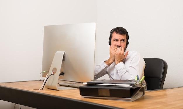 Telemarketer homem em um escritório é um pouco nervoso e com medo de colocar as mãos à boca Foto Premium