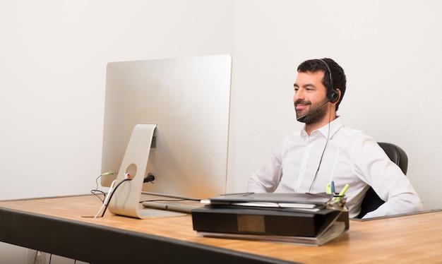 Telemarketer homem em um escritório posando com os braços no quadril e rindo olhando para a frente Foto Premium