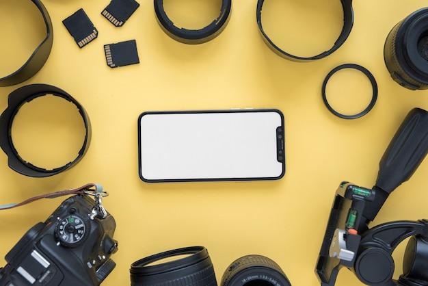 Telemóvel com tela em branco, rodeada por acessórios de câmera moderna em fundo amarelo Foto gratuita