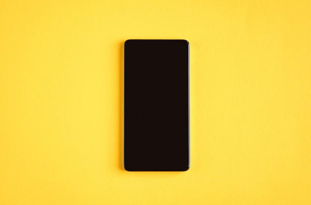 Telemóvel preto na superfície amarela, telefone móvel. Foto Premium