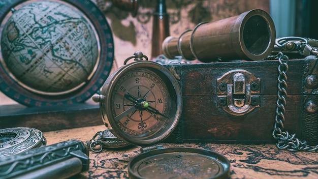 Telescópio vintage, bússola e antiga coleção no peito de madeira Foto Premium
