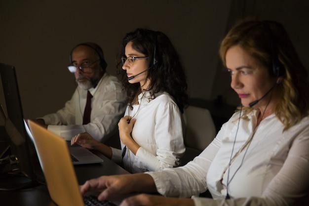 Teletrabalhadores em fones de ouvido no escritório escuro Foto gratuita