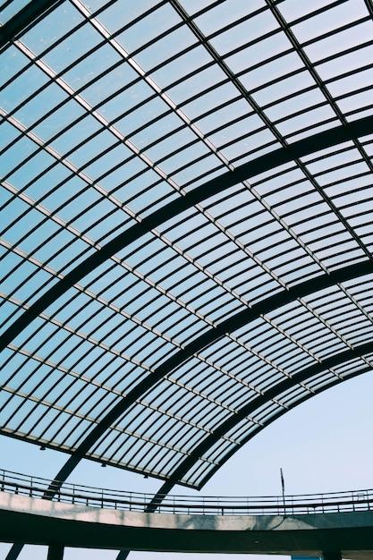Telhado de vidro de um edifício moderno sob o céu azul Foto gratuita