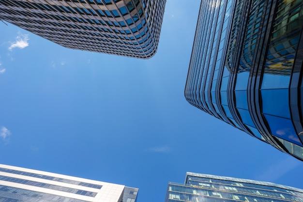 Telhados de vidro de centros de negócios são fotografados contra o céu azul Foto Premium