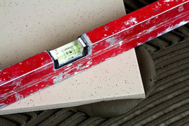 Telhas cerâmicas e ferramentas para ladrilhador. instalação de ladrilhos. melhoria home, renovação - adesivo para piso de cerâmica, argamassa, nível. Foto Premium