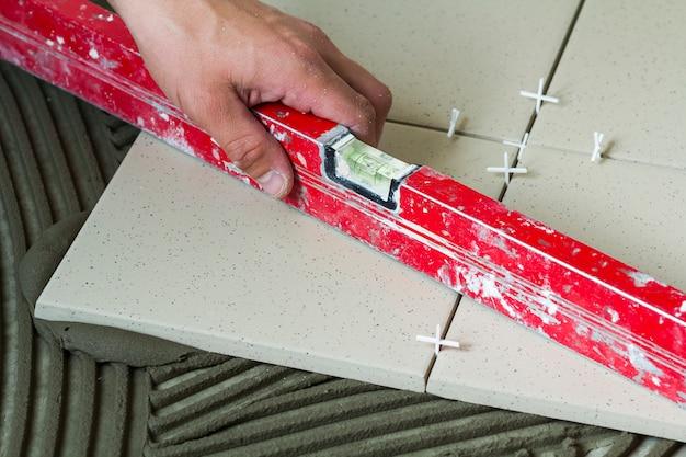 Telhas cerâmicas e ferramentas para ladrilhador. mão de trabalhador, instalação de pisos. melhoria home, renovação - adesivo para piso de cerâmica, argamassa, nível. Foto Premium