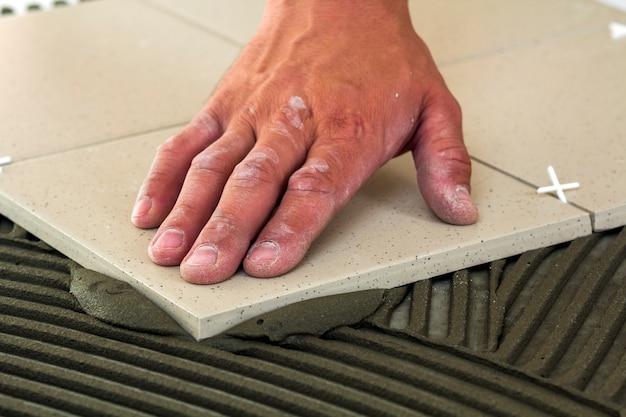 Telhas cerâmicas e ferramentas para ladrilhador. mão de trabalhador, instalação de pisos. melhoria home, renovação - adesivo para piso de cerâmica, argamassa. Foto Premium