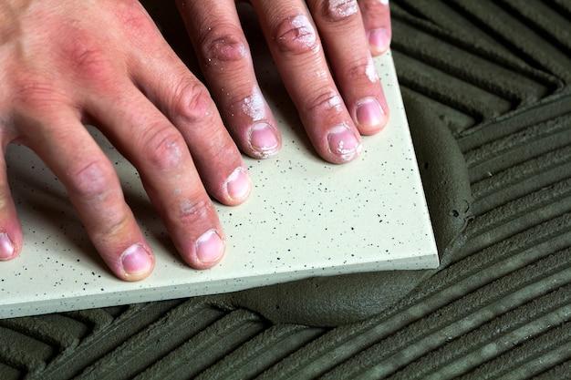 Telhas cerâmicas e ferramentas para ladrilhador. mão do trabalhador que instala telhas de assoalho. melhoria home, renovação - adesivo para piso de cerâmica, argamassa, nível. Foto Premium