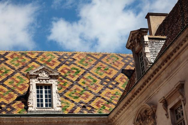 Telhas de telhado cerâmicas tradicionais em uma construção do governo em dijon, borgonha, frança. Foto gratuita