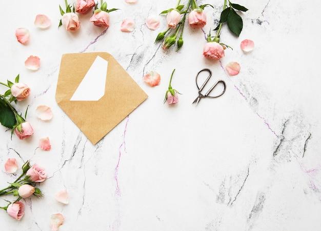 Tema de férias de primavera, rosas e carta sobre um fundo de mármore branco Foto Premium