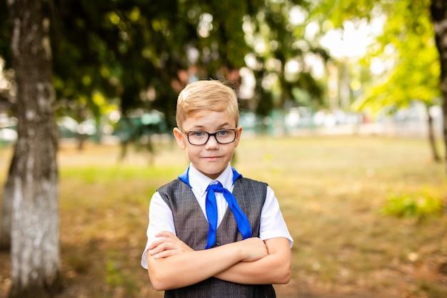 Tema educacional: retrato de um estudante com grandes óculos escuros e gravata azul. quintal da escola, início das aulas Foto Premium