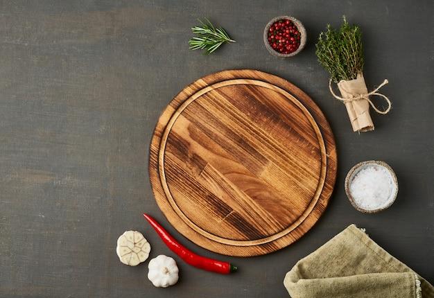 Tempero de alimentos. menu, receita, mock up. tábua de cortar redonda de madeira Foto Premium