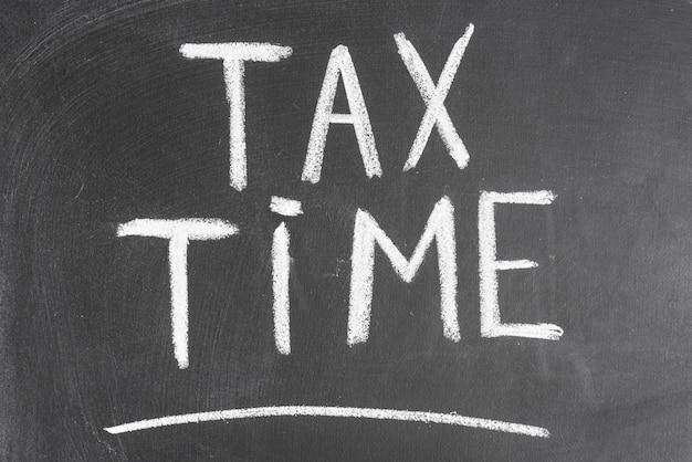 Tempo de imposto escrito na tabela preta com giz Foto gratuita