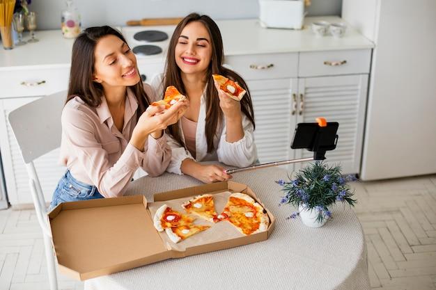 Tempo de pizza de ângulo alto com mulheres Foto gratuita