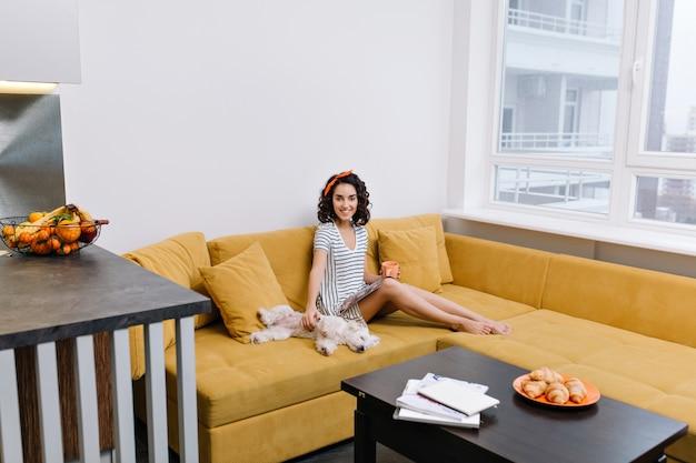 Tempo de relaxamento em apartamento moderno de mulher jovem e feliz relaxando no sofá laranja. revista, xícara de chá, animais domésticos, humor alegre, sorriso, emoções verdadeiras Foto gratuita