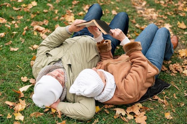 Tempo do casal sênior para ler enquanto está sentado no campo com folhas Foto gratuita