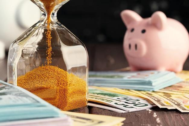 Tempo e dinheiro conceito de negócio. ampulheta e dinheiro Foto Premium