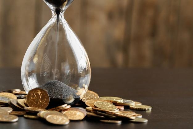 Tempo é dinheiro conceito. feche acima da ampulheta com moedas de dinheiro  | Foto Premium
