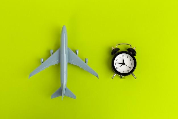 Tempo para viajar conceito. passageiro de brinquedo de jato de avião de plástico com despertador Foto Premium
