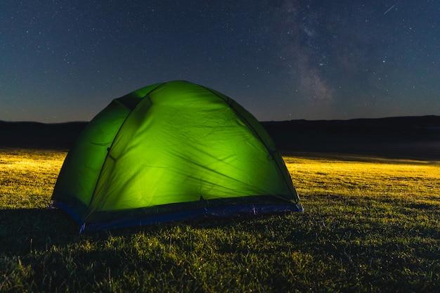 Tenda com luz no campo à noite com estrelas Foto Premium