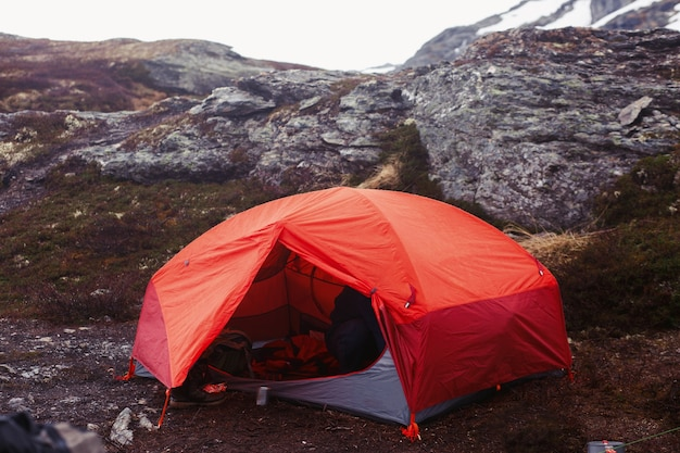 Tenda vermelha fica no chão em algum lugar nas montanhas Foto gratuita