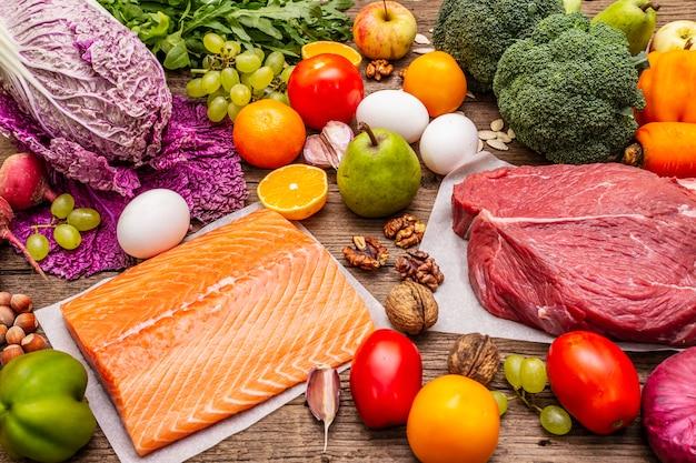 Tendência da dieta paleo / pegan. conceito de comida equilibrada saudável. conjunto de produtos frescos, carne crua, salmão, legumes e frutas Foto Premium