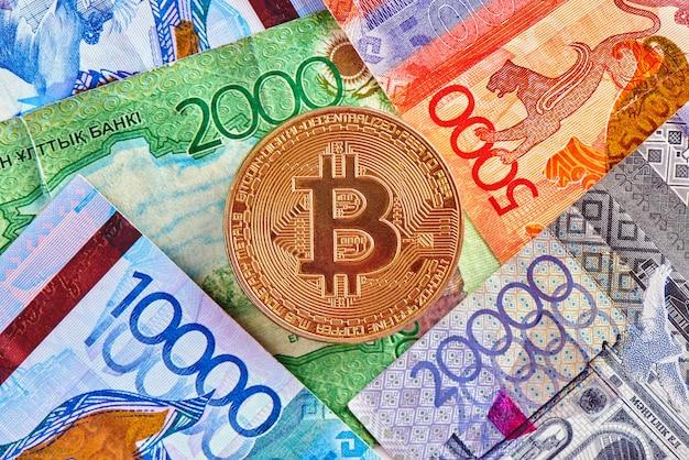 Tenge cazaque dinheiro e criptomoeda bitcoin close-up. conceito de investimento em moeda virtual digital na internet Foto Premium