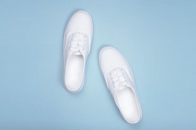 Tênis branco em azul, plano leigos. sapato de tendência da moda, loja de sapatos conceito Foto Premium