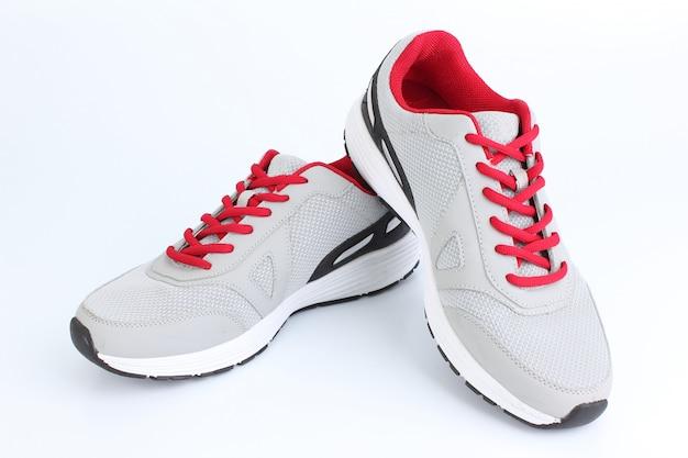 Tênis cinza com laços vermelhos sobre um fundo branco Foto Premium