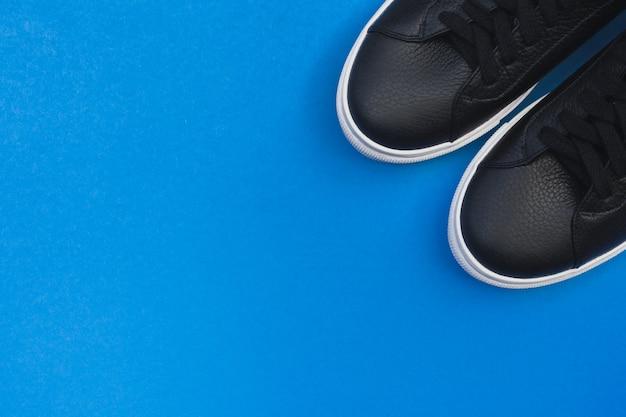 Tênis pretos sobre fundo azul. vista plana leiga, vista superior fundo mínimo. Foto Premium