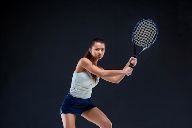 Tenista linda garota com uma raquete em fundo escuro Foto gratuita