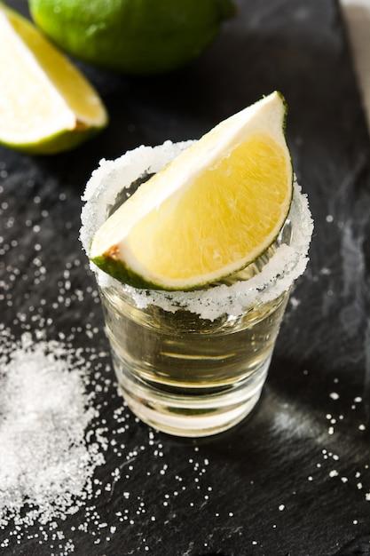 Tequila mexicana de ouro com limão e sal no preto. Foto Premium