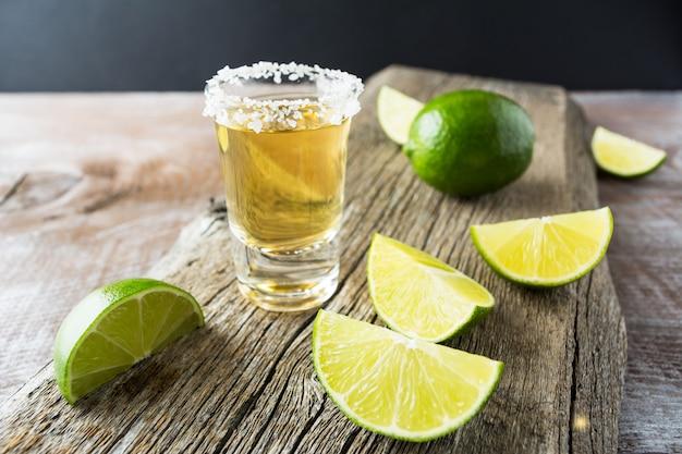 Tequila tiro com limão no fundo de madeira rústico Foto Premium