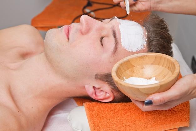 Terapeuta, aplicando, um, máscara face, para, um, bonito, homem jovem, em, um, spa Foto Premium