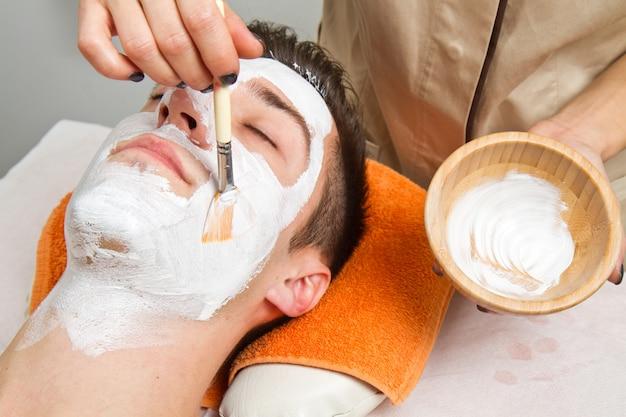 Terapeuta, aplicando, um, máscara rosto, para, um, bonito, homem jovem, em, um, spa, usando, um, escova cosmética Foto Premium