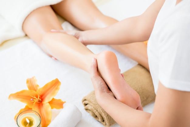 Terapeuta dando relaxante tratamento de massagem na perna de óleo tailandês para uma mulher no spa Foto Premium