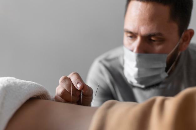 Terapeuta de close-up usando máscara médica Foto gratuita