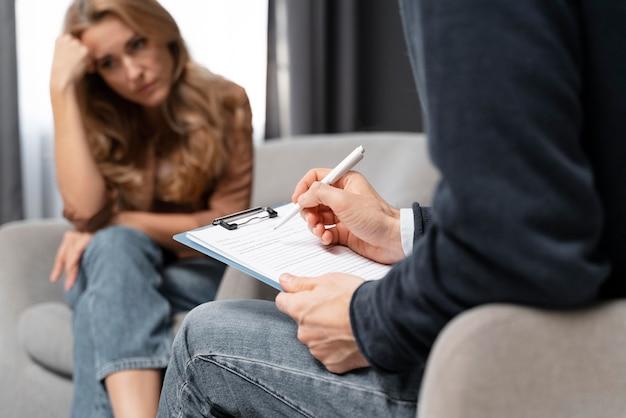 Terapeuta de meio tiro tomando notas perto de uma mulher Foto gratuita