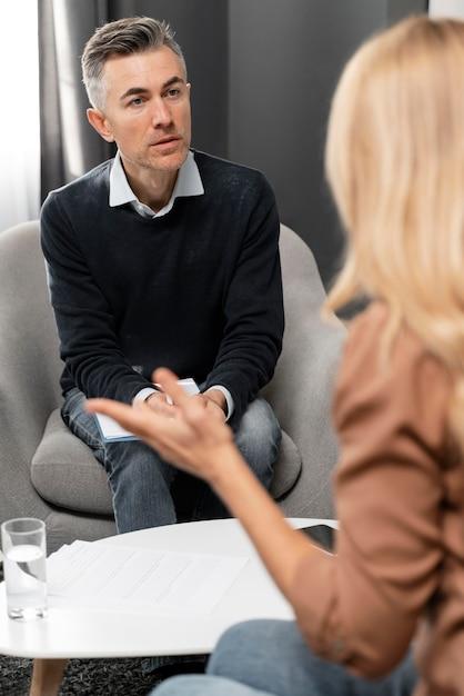 Terapeuta de tiro médio com prancheta olhando para uma mulher Foto gratuita