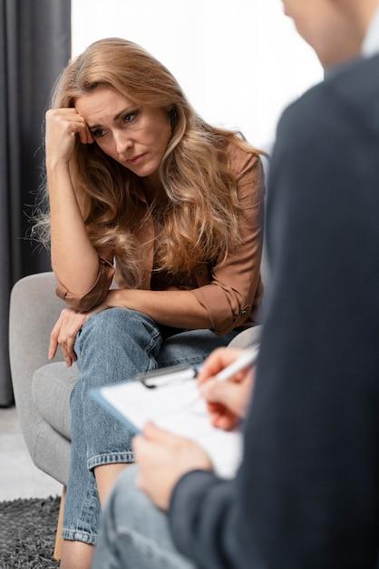 Terapeuta fazendo anotações perto de uma mulher Foto gratuita