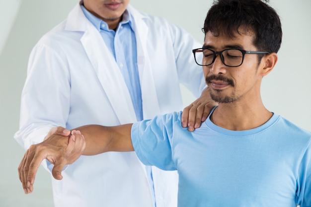 Terapeuta fazendo tratamento de cura na mão do homem / ombro Foto Premium
