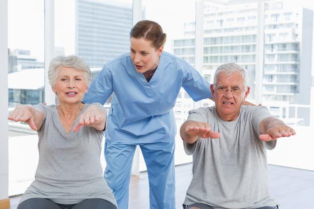 Terapeuta feminina, auxiliando o casal sênior com exercícios Foto Premium