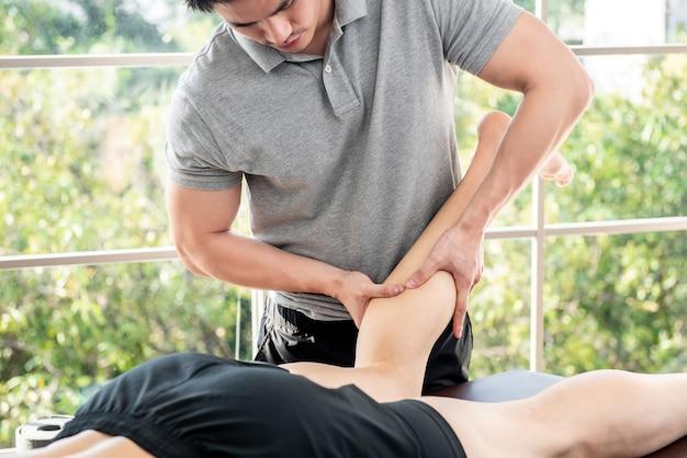 Terapeuta masculina, dar, perna, massagem, para, atleta, paciente, em, clínica Foto Premium