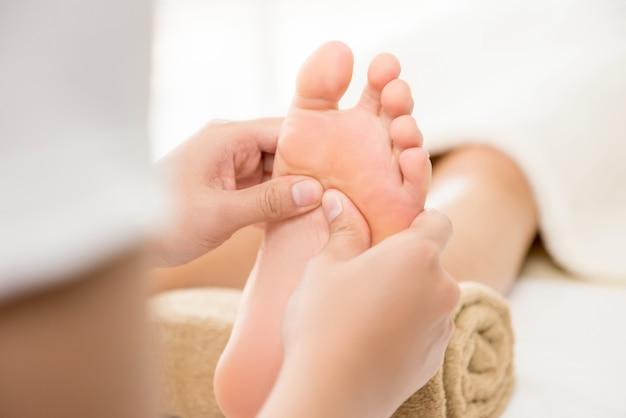 Terapeuta profissional dando massagem tailandesa tradicional nos pés para uma mulher Foto Premium