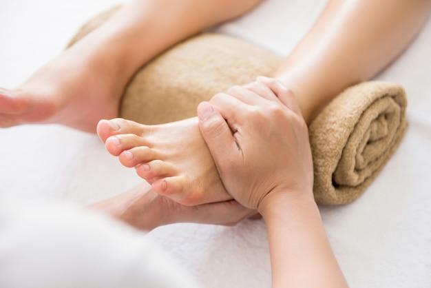 Terapeuta profissional dando reflexologia relaxante massagem nos pés tailandesa para uma mulher em spa Foto Premium